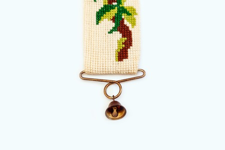 Old vintage dutch embroidery cross with red and green threads on the yellow canvas. Holland's needlework with forged copper bell. Stock Photo
