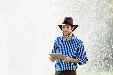 Farmer using digital tablet computer on sprinkler system background. A young agronomist is on the plantation and checks quality of the crop. Stock Photo