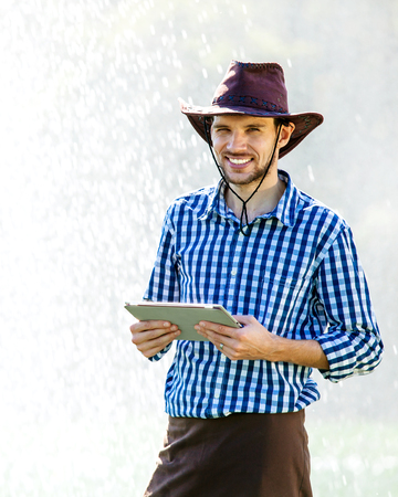 Farmer using digital tablet computer on sprinkler system background. A young agronomist is on the plantation and checks quality of the crop. Imagens