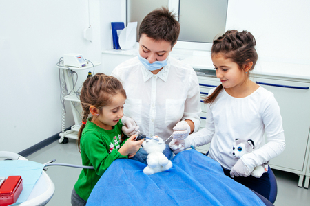 The doctor shows the little girls the procedure for the treatment of teeth. Dentist woman save atmosphere of calm and purity especially for young patients. 写真素材 - 120635933