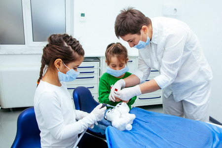 The doctor shows the little girls the procedure for the treatment of teeth. Dentist woman save atmosphere of calm and purity especially for young patients. 写真素材