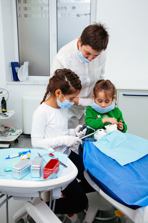 The doctor shows the little girls the procedure for the treatment of teeth. Dentist woman save atmosphere of calm and purity especially for young patients. 写真素材 - 120635964