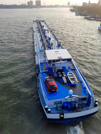 Top view of big blue barge in the port on blue sea background. Cargo transportation and transport services by sea.