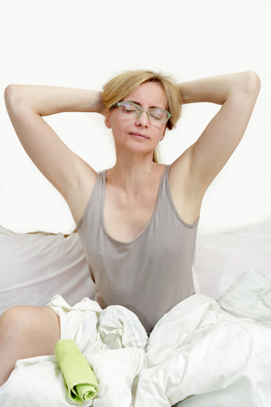 Middle aged fifty plus woman with the towel absorbs sweat from the skin. Real portrait woman with tides in the period of menopause.