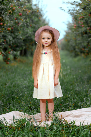 Little girl in a white dress and hat in an apple garden standing on a plaid.