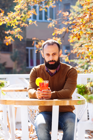 Beard man is sitting in a cafe on the background of autumn leaves. Brunette in yellow sweater drinks and get warm mulled wine in a cafe or garden.