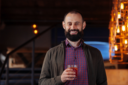 Happy laughing bearded man in a cafe drinking mulled wine. Businessman in the office in a loft style holds a glass with a red hot drink.