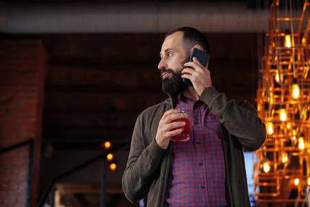 Bearded man in a cafe drinking mulled wine. Businessman in the office in a loft style holds a glass with a red hot drink.