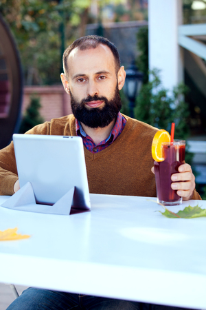 Bearded man in a cafe drinking mulled wine. Businessman works in office, holds a glass with a red hot drink and uses tablet.