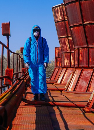 Men in blue protective overall at the old destroyed factory. Concept of environmental polution and ecological catastrophe.