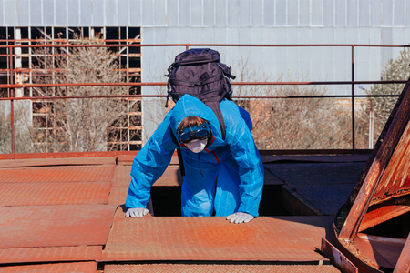 Men in blue protective overall at the old destroyed and lost factory. Concept of environmental polution and ecological catastrophe. Stock fotó