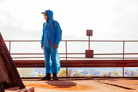 Men in blue protective overall at the old destroyed and lost factory. Concept of environmental polution and ecological catastrophe. Stock Photo