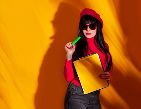 Business woman in red beret on yellow background with shadow. The seller or manager in red t-shirt on orange wall with document table, copy space.