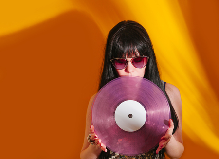Young DJ woman with pink vinyl enjoys music. Glamorous hippie brunette on hot yellow background with sunlight and shadow.