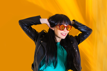 Portrait of smiles girl with red sunglasses. Positive woman on yellow background with sunlight and shadow. Stock Photo