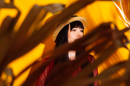 Young woman in red dress and hat with tropical leaves. Glamorous brunette on hot yellow background with sun light and shadow. Stockfoto