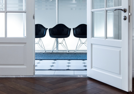 Modern black chair in white room interior parquet wood floor. Three chairs in reception.