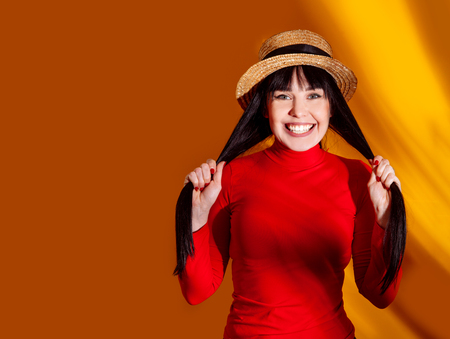 Young happy woman in red dress and hat with tropical leaves. Glamorous brunette on hot yellow background with sun light and shadow.
