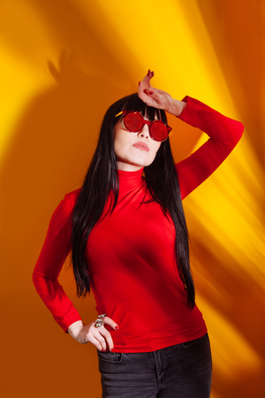 Young woman in red glasses on tropical leaves background. Glamorous brunette on hot yellow background with sun light and shadow. 写真素材
