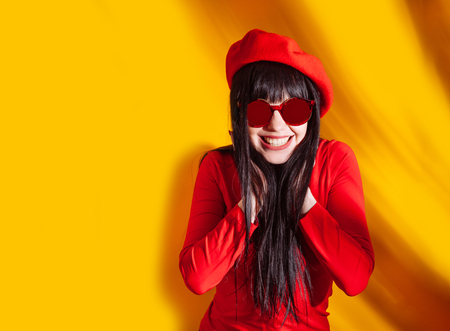 Young woman in red glasses and hat with shadow from tropical leaves. Glamorous brunette on hot yellow background with sun light and shadow.