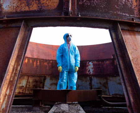 Men in blue protective overall on lost soviet factory. Concept of environmental polution and ecological catastrophe.