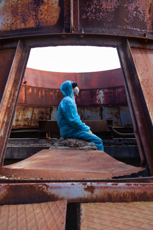 Sad men in blue protective overall on lost soviet factory. Concept of environmental polution and ecological catastrophe.