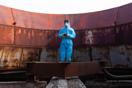 Men in blue protective overall on lost soviet factory makes photos by mobile phone. Concept of environmental polution and ecological catastrophe. Dack tourism.
