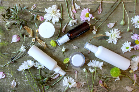 Cosmetics container, jars and flowers on green wooden background, top view. White dispensers and bottles with wild flowers on old vintage table.