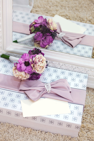 Pink roses on the wedding dress background with greeting card or invitation. Purple peonies on gift box. 写真素材