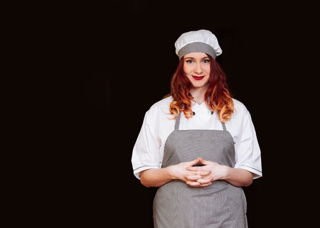 Portrait of young attractive cook woman dressed white uniform isolated on black background. Funny Chef with happy emotions.