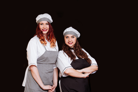 Portrait of young attractive cook women dressed white uniform isolated on black background. Funny Chefs with happy emotions.