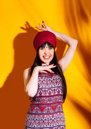 Beautiful indian woman on yellow studio background with shadow and sun light. Young emotional krishna dressed turban and red dress.