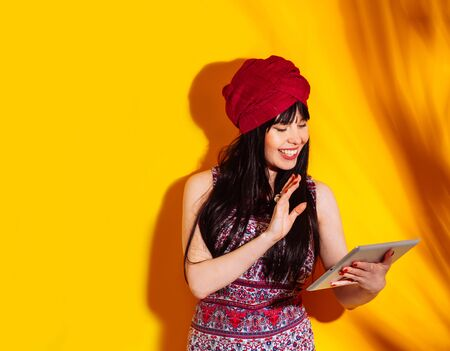 Beautiful indian woman on yellow studio background with shadow and sun light. Young emotional krishna dressed turban and red dress uses tablet.