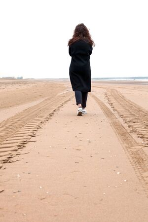 Lonely girl on the background of the sea steps by sand's road. Woman walking to the North sea, wind, rain. Stock Photo