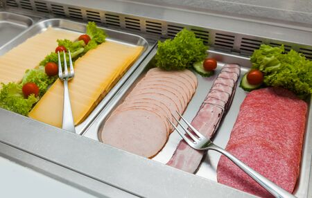Breakfast in hotels buffet. Fresh vegetables, sausage, salami, meat into refrigerator for clients. 写真素材