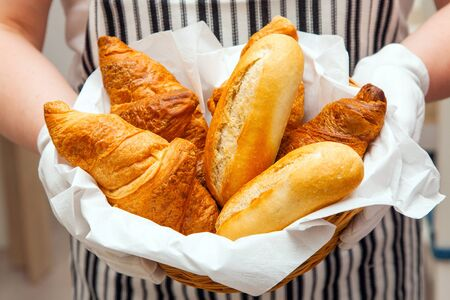 Fresh buns and croissants in basket on the canvas background. Baker dressed apron holds tasty and appetizing pastries for breakfast in hotel.