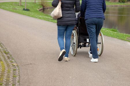 Caring daughter and nurse and old person in wheel chair walking green nature. Help for retired concept.