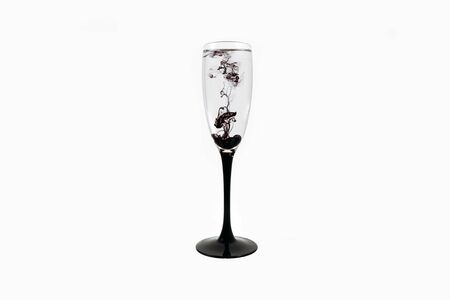 Wine glass on white background with black color paints inside. Fougere for champagne with black smoke and streak.