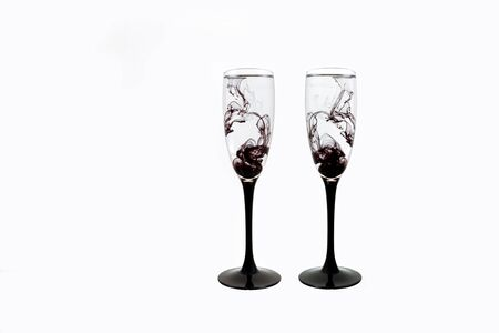 Two Wine glasses on white background with black color paints inside. Fougeres for champagne with black smoke and streak.