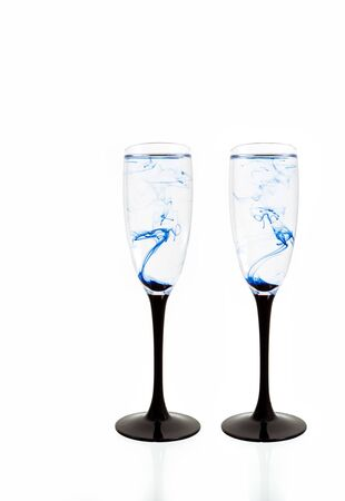 Two wine glasses on white background with blue color paints inside. Fougeres for champagne with smoke and streak.