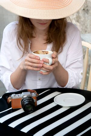 Tourist woman with vintage digital camera shooting and drinking coffee at city street cafe terrace. Close-up of female hands with a small digital camera and a cup of coffee.
