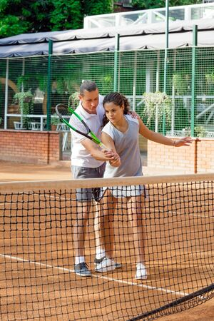 Girl teenager with long curly hair with a racket in his hands. Girl tennis player on the court in summer with trainer
