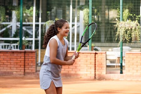 Girl teenager with long curly hair with a racket in his hands. Girl tennis player on the court in summer.