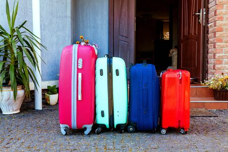 Four multicolored suitcases stand in front of the house. luggage near the family car ready for the holidays trip.
