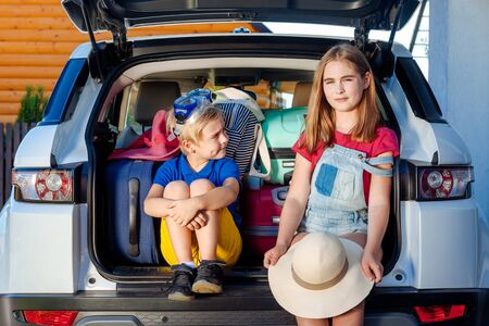 Little sister and brother are sitting in the trunk of a car with suitcases. Travel by car family trip together vacation. Laughing Girl and boy ready to travel with family.