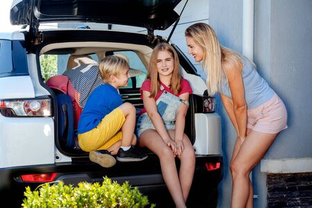 Mother, girl and boy are loading multicolored suitcases in the trunk of car. Family with a dog labrador stand near the car and ready for travel.
