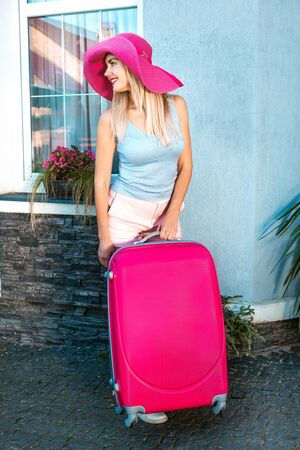 Woman traveler with pink suitcase on blue color background. Beautiful blonde girl with a pink hat and baggage on the background of a house or hotel.