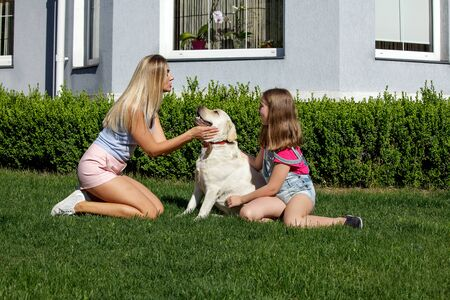 Family with a large Labrador Retriever in the background of a house on the lawn. Mother and daughter with pet sitting on the grass at the summer park.