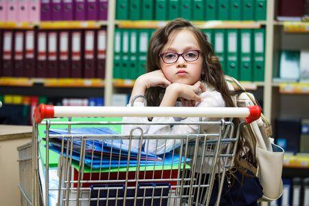 Una niña está comprando material de oficina para la escuela. Colegiala con gafas en un supermercado con carro. Concepto de regreso a la escuela. Foto de archivo