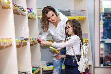 Mutter und Tochter kaufen Schulnotizbuch und Schreibwaren im Einkaufszentrum. Schulmädchen mit Brille und Rucksack in einem Supermarkt. Standard-Bild